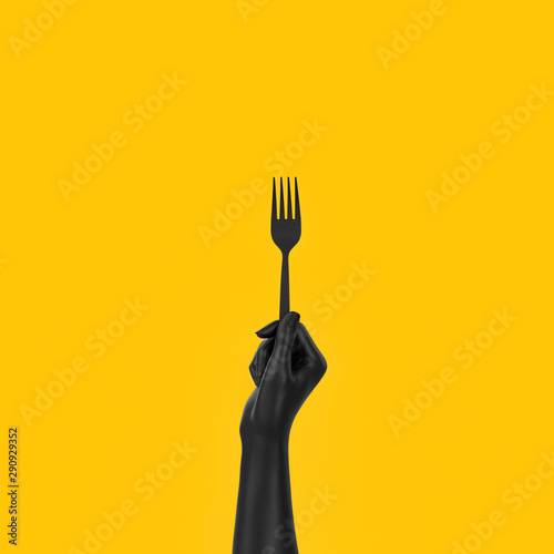 Fotografiet Black Hand holding fork isolated on yellow, abstract food concept banner