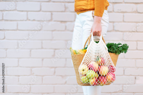 Zero waste concept with copy space. Woman holding straw basket and reusable mesh shopping bag withapples, vegetables, white brick background. Eco friendly mesh shopper. Copy space