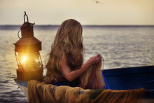 Girl With Long Hair In An Old Boat At Sea. Marine Antique Lantern And Nets In An Old Boat. Magical Fabulous Photo Of A Fisherman Girl.