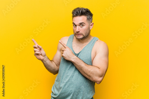 Obraz na plátně  Young fitness man against a yellow background shocked pointing with index fingers to a copy space