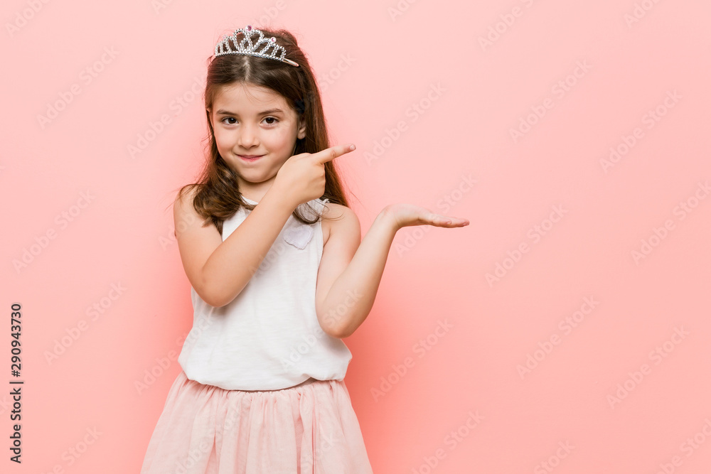 Fototapety, obrazy: Little girl wearing a princess look excited holding a copy space on palm.