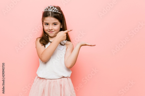 Little girl wearing a princess look excited holding a copy space on palm Fototapet