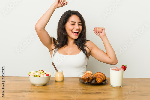 Fotografie, Tablou Young curvy woman taking a breakfast celebrating a special day, jumps and raise arms with energy
