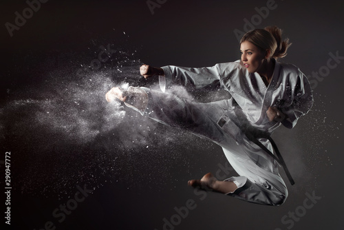 фотография Karate girl bounces and makes a kick