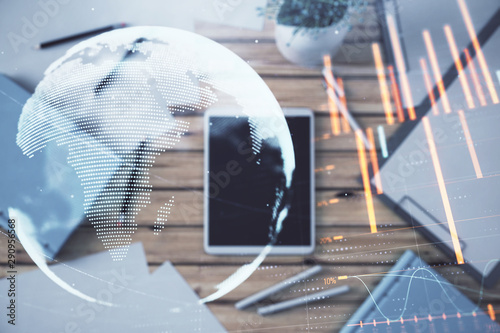 Double exposure of forex chart and world map on digital tablet laying on table background. Concept of market analysis