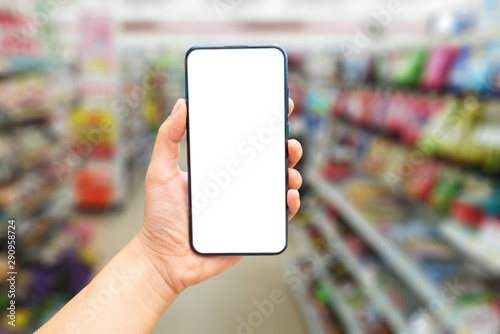 Fototapeta  Mock up image of A hand holding a blank screen of smartphone on blurred​ background