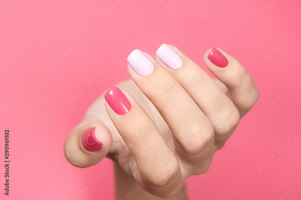 Fototapety, obrazy: Closeup view of single beautiful white hand of caucasian adult woman with trendy asymmetric two colours bright manicure isolated on pink background. Horizontal color photography.