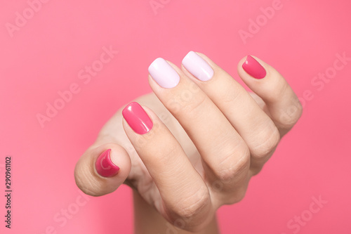 Closeup view of single beautiful white hand of caucasian adult woman with trendy asymmetric two colours bright manicure isolated on pink background. Horizontal color photography.
