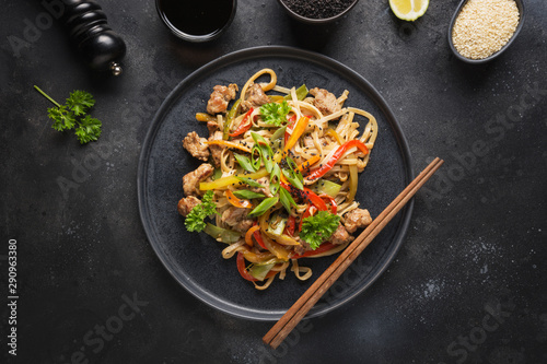 Udon stir-fry noodles with pork bowl and vegetables on black stone background Canvas Print