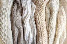 Bunch Of Knitted Warm Pastel Color Sweaters With Different Vertical Knitting Patterns Hanging In Bunch, Clearly Visible Texture. Stylish Fall / Winter Season Knitwear Clothing. Close Up, Copy Space.
