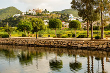 River Walk In Santa Eulalia With Town Church View And Tree Reflection