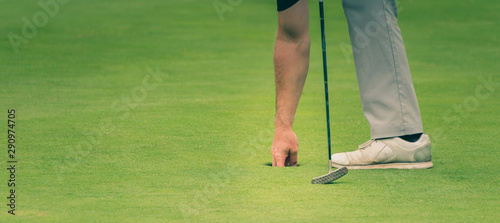 Golfer is taking the ball out of the hole.