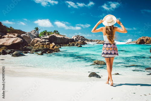 Fototapeta  A young girl standing in shallow water on La Digue island, Seychelles
