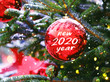 New Year 2020 concept. red ball with numbers 2020, symbol of coming new year. red ball hanging on fir branches, winter natural snow background. Happy New Year card. soft selective focus