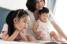 Beautiful Asian Mother Reading...