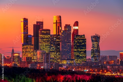 Wonderful modern city view with the orange sky and illuminated skyscrapers after sunset