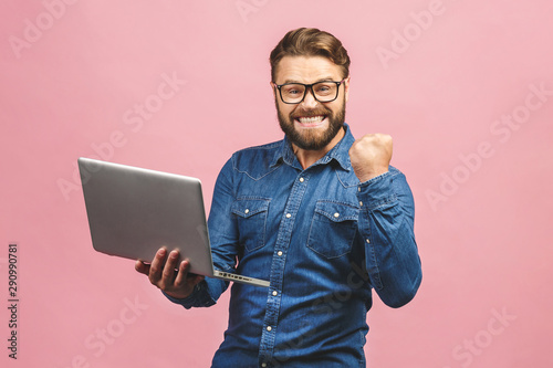 Fotografie, Obraz  I'm a winner! Happy man holding laptop and celebrating his success over pink background