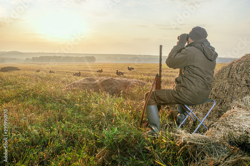 Hunter with a binoculars and a hunting gun in the autumn Canvas Print