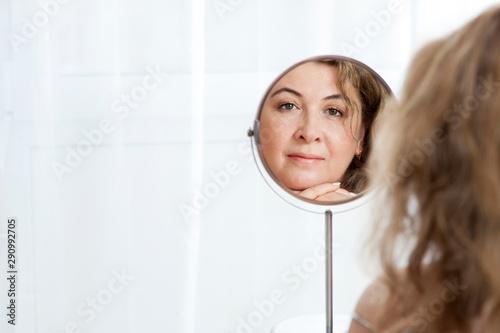 Fotografía  Beautiful mature Caucasian woman looking in the mirror