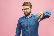 Stylish Fashionable Male Poses Indoors Against Pink Background, Assess Project, Shows Sign Of Dislike, Looks With Negative Expression And Disapproval. Disagreement, Disgust And Negative Expressions