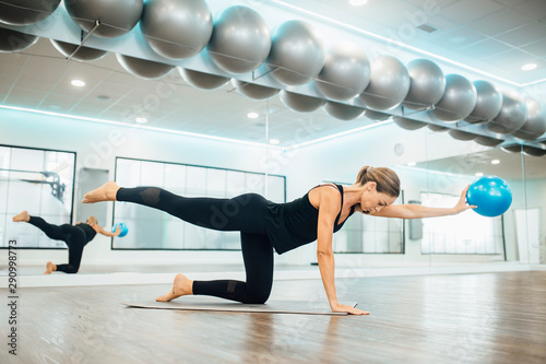 Fotografie, Tablou  attractive woman doing pilates exercises with a fit ball in the gym