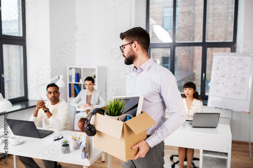 Fotomural business, firing and job loss concept - sad fired male office worker with box of