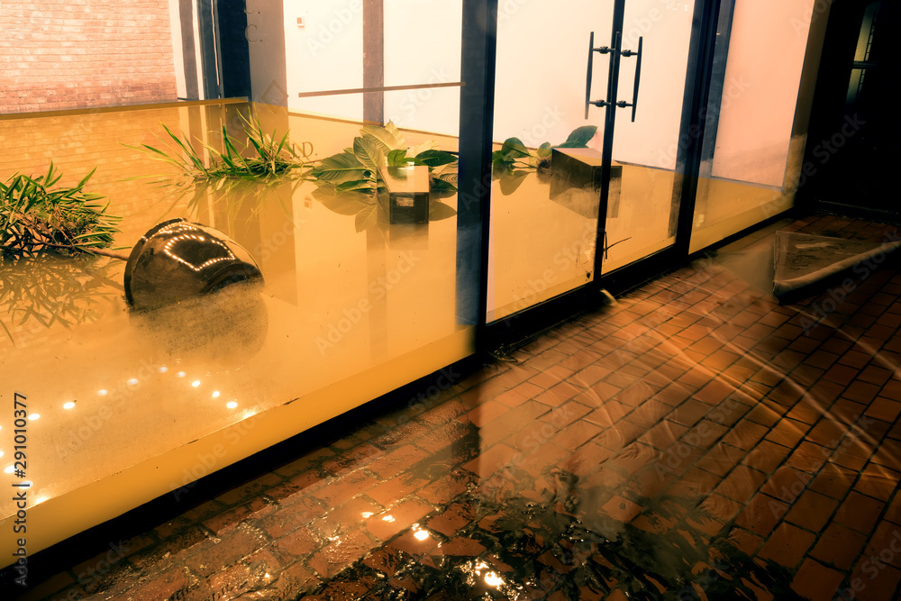 Fototapeta  Water flowing through doors from a flooded office. Effects Tropical depression Imelda. Houston, Texas, US
