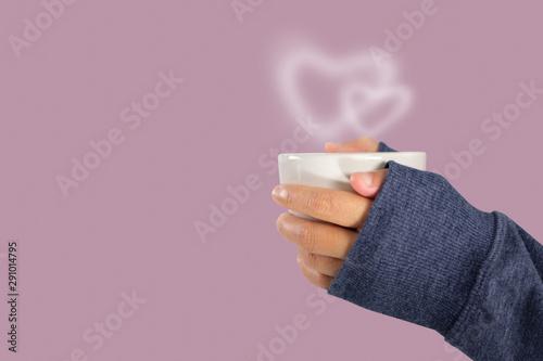 Fototapeta  Hand holding a hot coffee cup with heart shaped smoke.