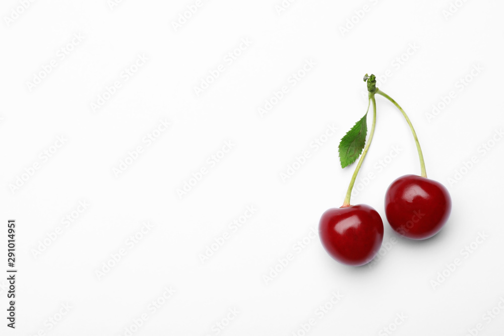 Fotografie, Obraz Delicious ripe sweet cherries with leaf on white background
