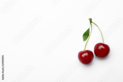 Tablou Canvas Delicious ripe sweet cherries with leaf on white background