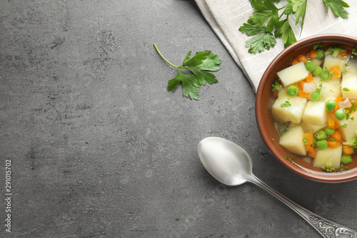 Fotografie, Obraz  Bowl of fresh homemade vegetable soup served on grey table, flat lay
