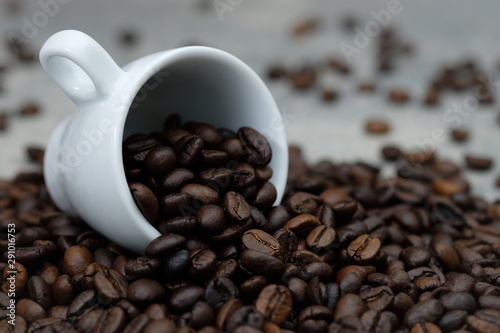 Coffee beans spilled out of white ceramic cup Canvas Print