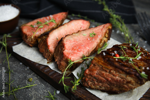 Board with slices of grilled meat on grey table, closeup - 291017585