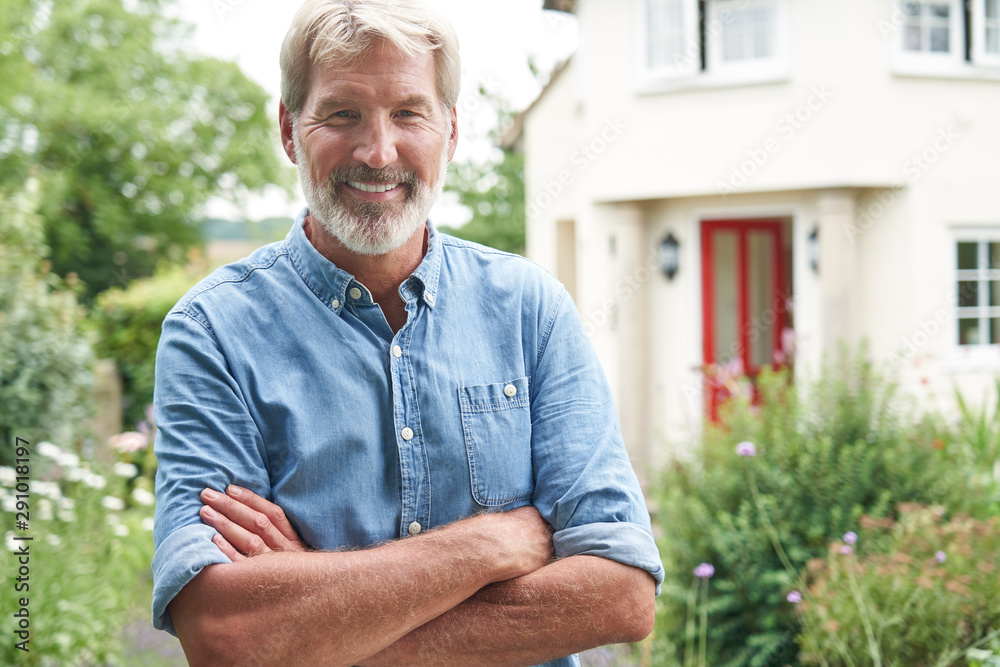 Fototapeta Portrait Of Mature Man Standing In Garden In Front Of Dream Home In Countryside