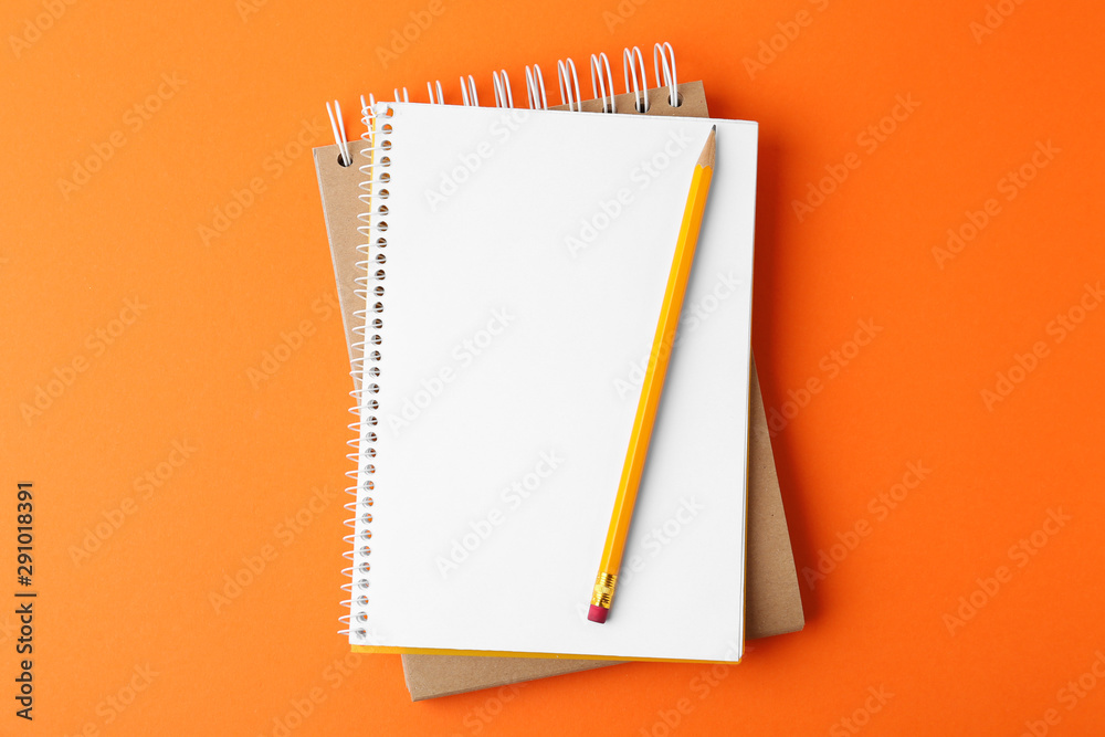 Fototapeta Notebooks with pencil on orange background, top view