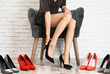 canvas print picture - Woman trying on different shoes near white brick wall, closeup