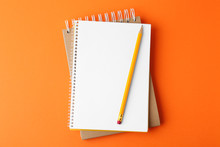 Notebooks With Pencil On Orang...