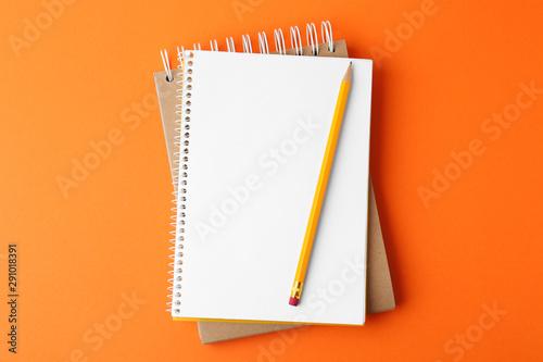 Fototapeta Notebooks with pencil on orange background, top view obraz