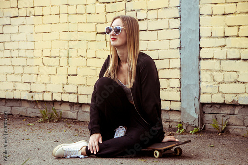 Sportive fashion woman sitting on skateboard. Young Girl in sunglasses with longboard on city streets