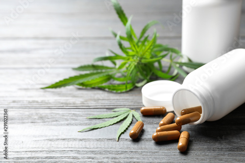 Fotografia Hemp leaves and bottle with capsules on grey wooden table