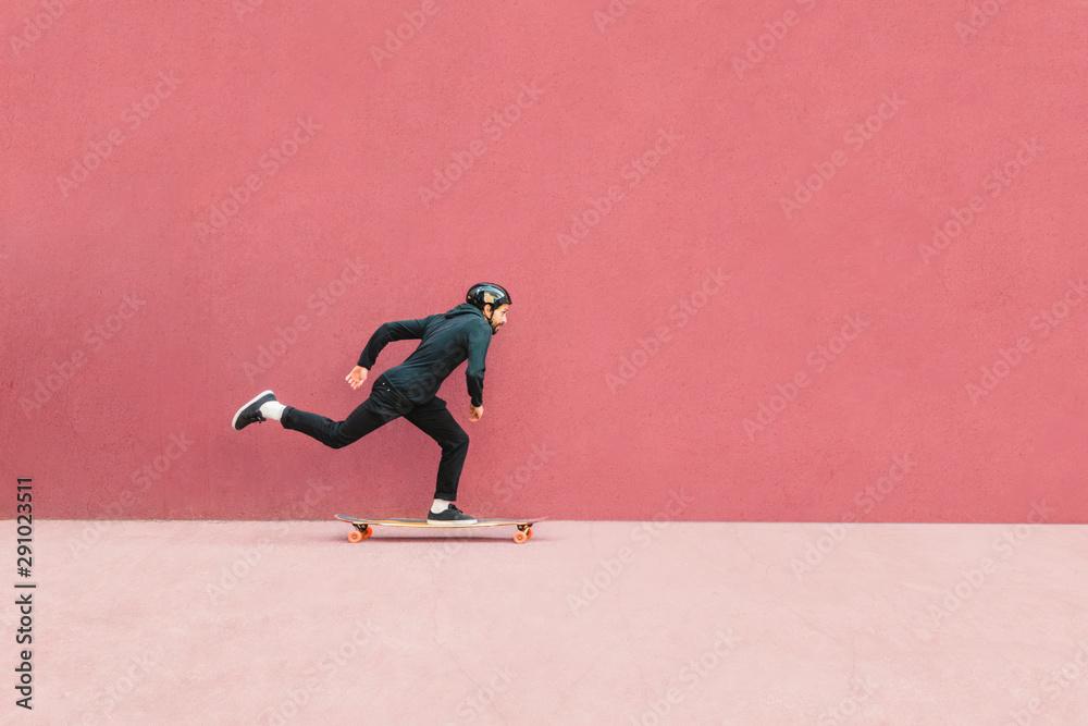 Fototapety, obrazy: Full length of man skateboarding against wall