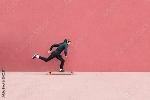 Full length of man skateboarding against wall