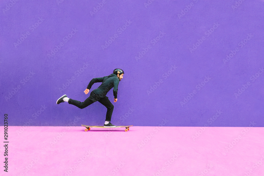 Fototapeta Full length of man skateboarding against wall