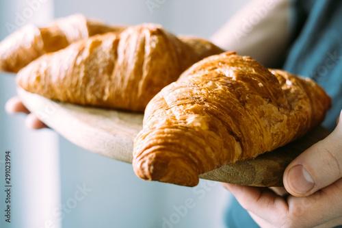 Foto auf Leinwand Brot Fresh croissants on a wooden tray