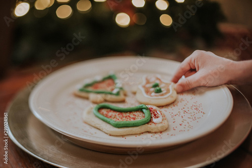Girl stealing Christmas Cookies off plate