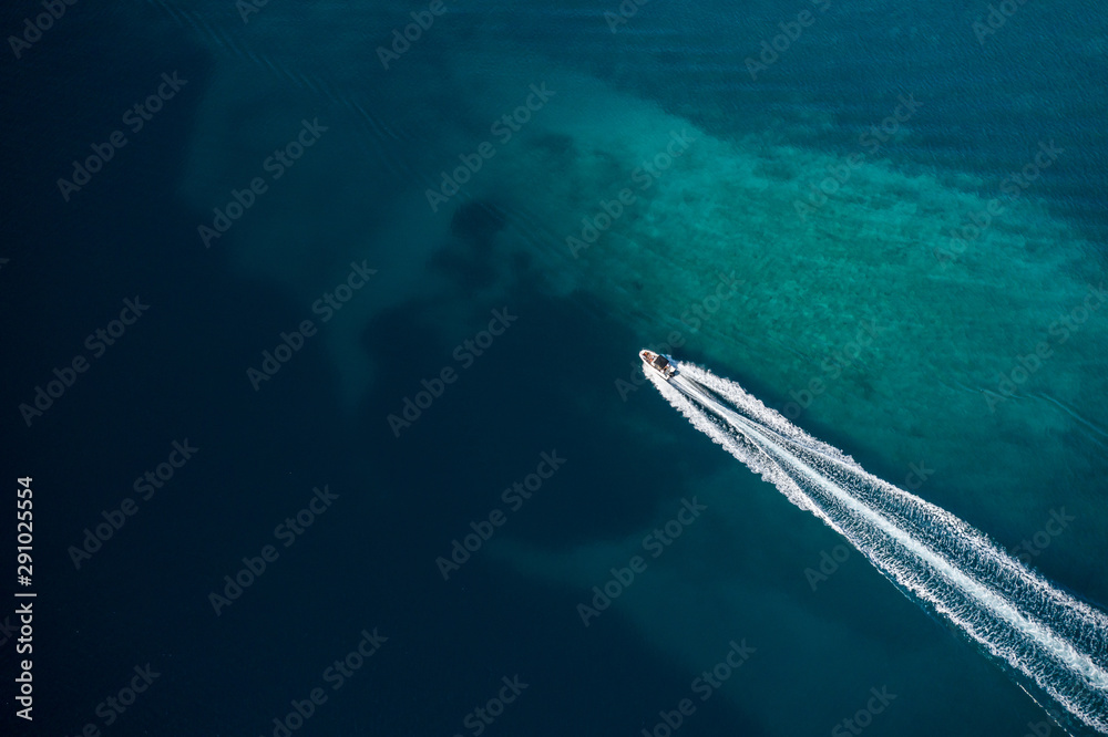 Fototapeta Aerial view of speed motor boat in shallow water