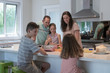 Family in kitchen together listening to little girl