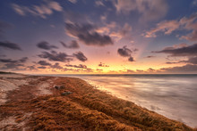 Golden Sunrise With A Sky Full Of Moving Clouds At The Caribbean Sea