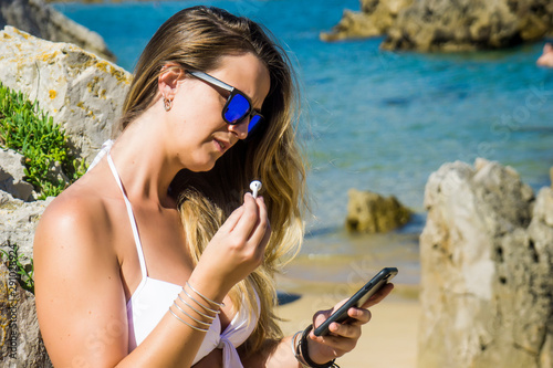 Valokuva pretty blonde woman with her headphones and her smart phone on the beach