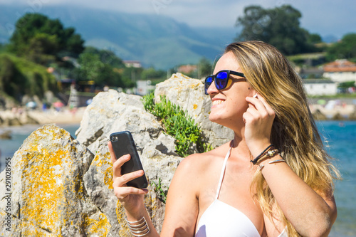 pretty blonde woman with her headphones and her smart phone on the beach Canvas-taulu
